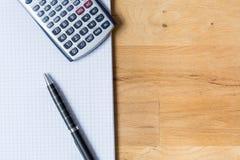 Bearbeiten Sie Schreibtisch mit Notizblock, Taschenrechner und Biro auf Holztisch stockfotografie