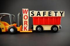 Bearbeiten Sie Sicherheitskonzept mit Holzklötzen auf orange Gabelstapler mit dunklem Hintergrund Stockfoto