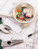 Bearbeiten Sie Werkzeuge und elektrischen Kasten mit Kabeln auf Bauzeichnung des Hauses Lizenzfreie Stockfotografie