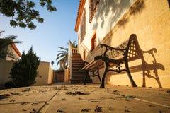 Bearbeitete schwarze Eisenbank im Yard mit gefallenen Blättern Lizenzfreies Stockbild