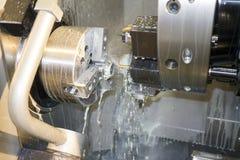 Bearbeta detaljen på CNC-drejbänken med kylmedlet Royaltyfri Foto