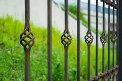 Bearbetat staket för gammal härlig dekorativ metall med det konstnärliga smidet Stryka rostigt ledstångbehov att måla och reparer fotografering för bildbyråer