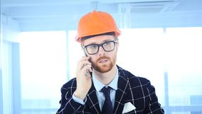 Beard Architectural Engineer Talking on Phone, Attending Call at Work. 4k , high quality Royalty Free Stock Images