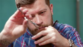 Beard barber making haircut to hipster stock footage