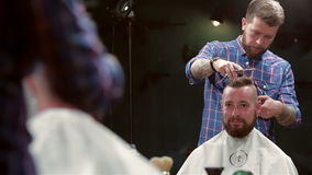 Beard barber making haircut to hipster stock video