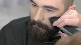 Beard grooming process, close up.