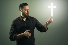 Beard handome man touchink a cross appearing in the air. Miracle of religion royalty free stock images