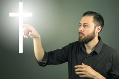 Beard handome man touchink a cross appearing in the air. Miracle of religion stock photography