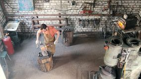 Beard man blacksmith in forge makes metal tools on iron anvil with hammer, top view. Small business stock video