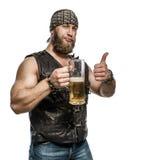 Beard man drinking beer from a beer mug. Stock Image