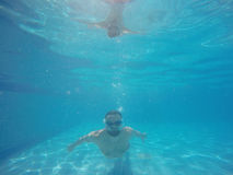 Beard man with glasses diving in a pool Stock Image