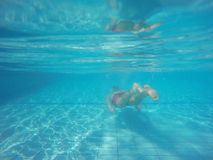 Beard man with glasses diving in a pool Stock Images