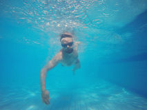 Beard man with glasses swimming under water in the pool Stock Photos