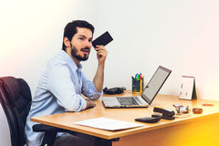 Beard man listening to voice mail. Listening to voice message at work. Sitting at workstation, using dress shirt Royalty Free Stock Image