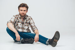 Beard man portrait sit on floor. Studio shot Royalty Free Stock Image