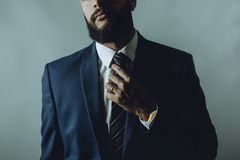 Beard man in a suit fixes tie royalty free stock photography