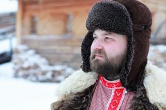Traditional winter costume of peasant medieval age in russia. Beard man in traditional winter costume of peasant medieval age in russia royalty free stock photography