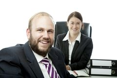 Beard man and woman at desk smiling Royalty Free Stock Photos