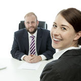 Beard man and woman smile. Beard business men brunette women at desk smiling stock images