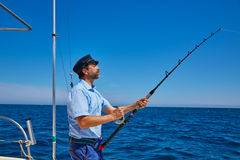 Beard sailor man fishing rod trolling in saltwater. In a boat trolling with captain cap Royalty Free Stock Image