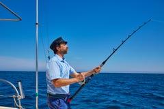 Beard sailor man fishing rod trolling in saltwater Royalty Free Stock Image
