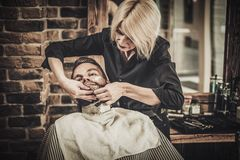 Beard shaving in barber shop Royalty Free Stock Images