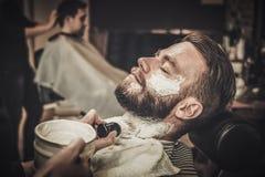 Beard shaving in barber shop Stock Image