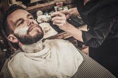 Beard shaving in barber shop Royalty Free Stock Image