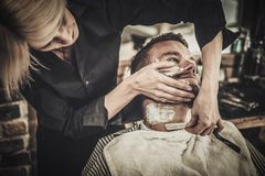 Beard shaving in barber shop Royalty Free Stock Photo