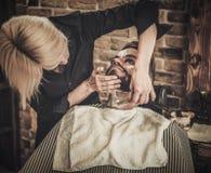 Beard shaving in barber shop Royalty Free Stock Images