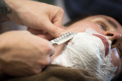 Beard shaving with straight razor. Interior shot of working process in modern barbershop. Close-up portrait of handsome young men getting beard shaving with royalty free stock image
