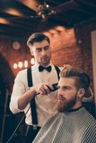 Beard styling for a handsome young guy at the barber shop. Hairdresser is attractive and wearing classic outfit, he is focused royalty free stock images