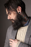 Beard and tatoos. Young man with long beard and tatoos posing in the studio Royalty Free Stock Images