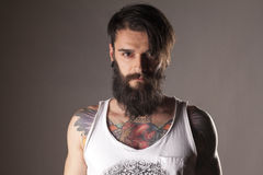 Beard and tattoos. Young man with beard and tattoos in a white sleeveless shirt Royalty Free Stock Images