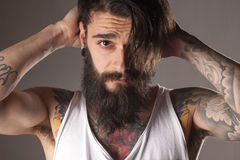 Beard and tattoos. Young man with beard and tattoos in a white sleeveless shirt stock photography