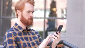 Beard Young Man Using Smartphone while Sitting Outdoor. 4k high quality, 4k high quality stock video