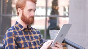Beard Young Man Using Tablet while Sitting Outdoor. 4k high quality, 4k high quality stock footage