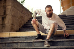 Beardead tattooed cool looking guy sitting in street on stairs Royalty Free Stock Photography