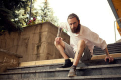 Beardead tattooed cool looking guy sitting in street on stairs Royalty Free Stock Photos