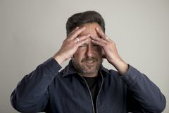 Adult Male Looking in Pain with Hands on Head Royalty Free Stock Photography