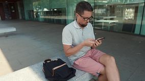 Middle aged man is swiping on screen of modern mobile phone, sits on street stock video footage