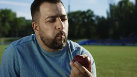 Happy man with apple on athletic field. Bearded adult man taking bite of juicy delicious apple and smiling at camera having rest after workout on field stock footage