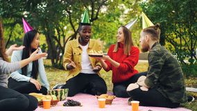 Bearded African American guy is having birthday party in park blowing candles on cake and laughing enjoying surprise royalty free stock images
