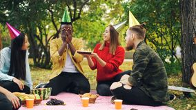 Bearded African American guy is having birthday party in park with candles on cake and laughing enjoying surprise royalty free stock photography
