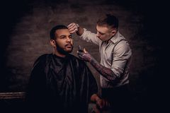 Old-fashioned professional tattooed hairdresser does a haircut to an African American client. on dark textured royalty free stock photography