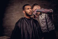 Old-fashioned professional tattooed hairdresser does a haircut to an African American client. on dark textured stock photo