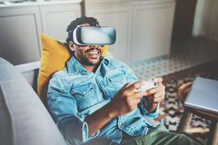 Bearded african man enjoying virtual reality glasses while relaxing on sofa.Happy young guy with vr headset or 3d Stock Image