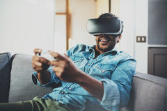 Bearded african man enjoying virtual reality glasses while sitting on sofa.Happy young guy with vr headset or 3d Stock Photos