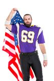 Bearded American football player with national flag, portrait. stock photo