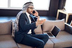 Arab businessman on lapton speaking on phone on couch at hotel room. Bearded arab businessman in suit on lapton speaking on phone on couch at hotel room Royalty Free Stock Photography